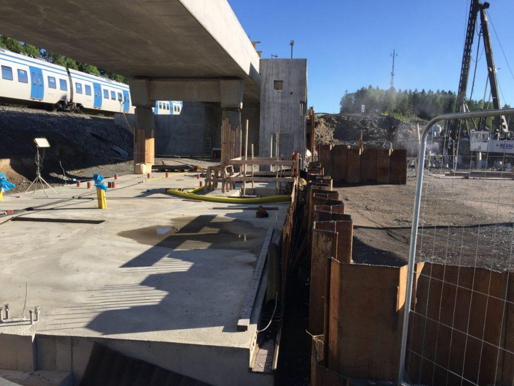 För stationshuset är grundläggningen pålad och spont för rulltrappan klar.
