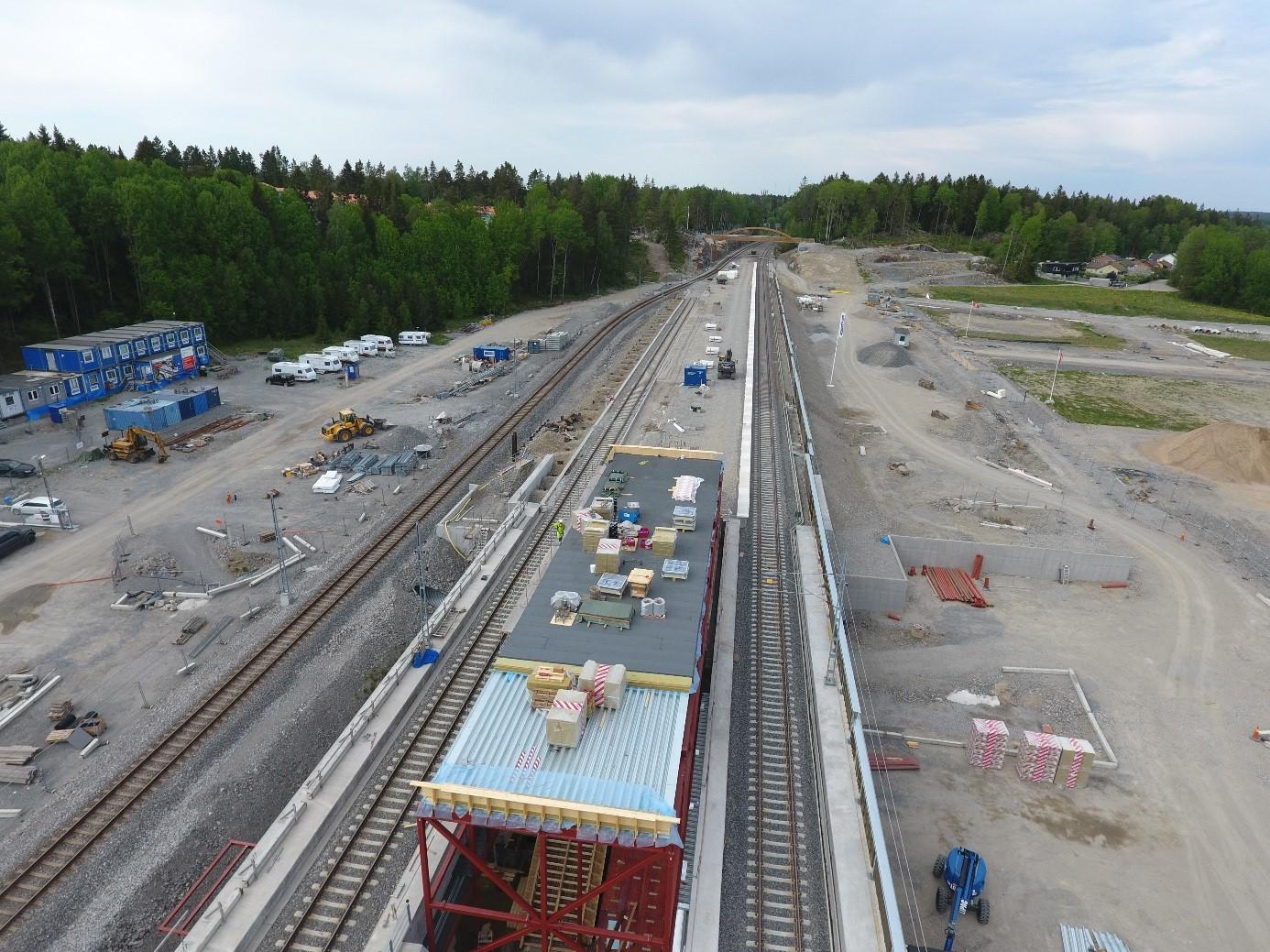 I mitten växer stationshuset fram med upp och nerspår på varsin sida. Det provisoriska spåret syns till vänster.